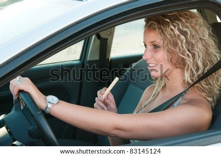 Young woman eating sweets while driving car