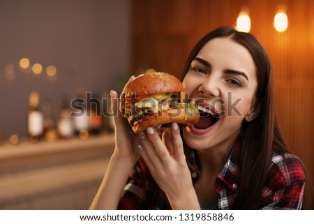Young woman eating tasty burger in cafe #1319858846