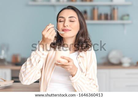 Young woman eating tasty yogurt at home Photo stock ©