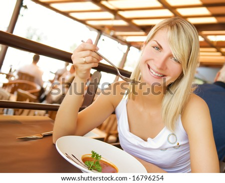 Young woman eating tomato soup in a restaurant
