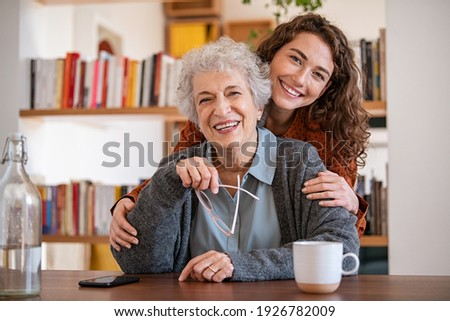 Young woman embracing senior mother at home and looking at camera. Portrait of happy adult granddaughter and grandmother embracing and smiling together. Lovely young woman hugging from behind grandma