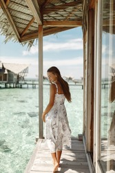 Young woman enjoy vacation on Maldives island while standing near wooden overwater bungalow by the sea
