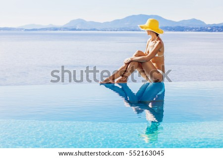 Young woman enjoying a sun in the infinity pool. Vacations and summer concept #552163045
