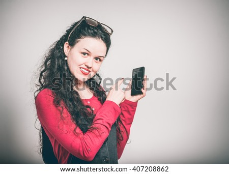young woman enjoying a touchscreen phone, dressed in a overalls, close-up isolated on a gray background #407208862