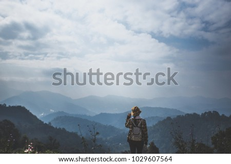 Young woman enjoying at a hill with blue sky. Sunrise in the morning. People have a trekking trips to a fog valley. Picture in vintage tone.
