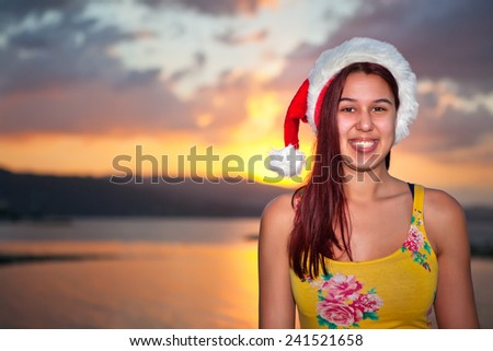Young woman enjoying Christmas on a sunset Jamaican beach.