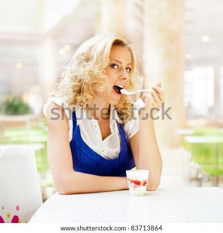 Young woman enjoying coffee time at mall cafe. Eating ice cream dessert