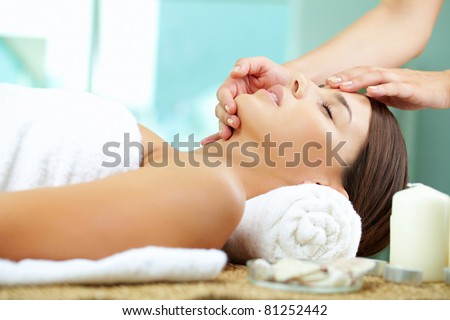 Young woman enjoying facial at spa salon