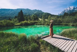 Young woman enjoying freedom on nature outdoors. Travel, Relaxation, Lifestyle Image. Amazing view on Zelenci (into English means - green) natural reserve in Slovenia, Europe. Nature background.
