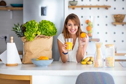 Young woman enjoying fresh orange juice. In her modern kitchen, a woman is about to drink her freshly-made smoothie, which is packed with vitamins. A healthy lifestyle is so much fun.