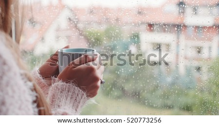 Young Woman Enjoying her morning coffee or tea, Looking Out the Rainy Window. Beautiful romantic unrecognizable girl drinking hot beverage at cozy home. Rainy Day Mood.
