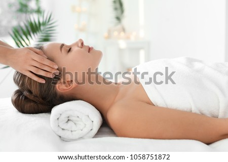 Photo of Young woman enjoying massage in spa salon