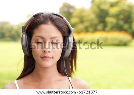 Young woman enjoying music with closed eyes