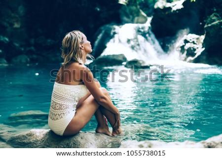 Young woman enjoying natural bathing by the Kawasan waterfall in Philippines