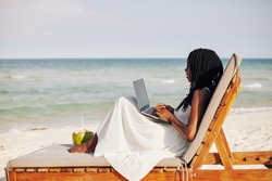 Young woman enjoying sitting on chaise-lounge, working on laptop and looking on sea waves