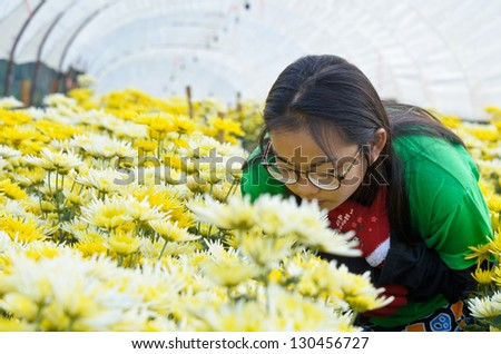 Young woman enjoying smell of flowers in the morning. Thailand