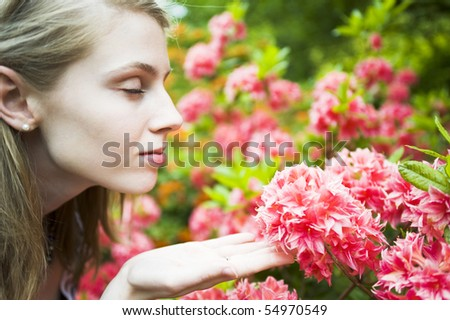 Young Woman Enjoying Smelling Pink Flowers