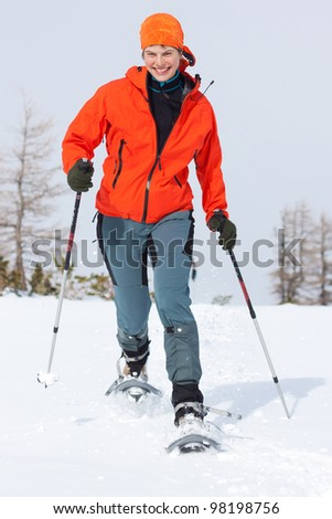 Young woman enjoying snowshoeing in sunny spring