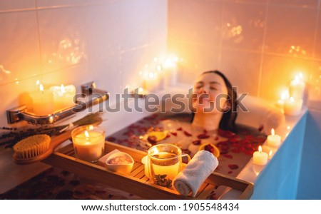 Young woman enjoying spiritual aura cleansing rose flower bath with rose petals and candles during full moon ritual. Body care and mental health routine.  Foto stock ©