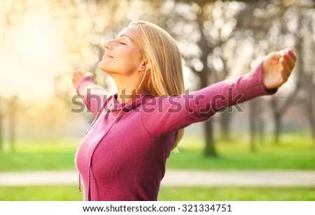 Young woman enjoying spring breeze in the park. The sun is shining.