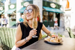 Young woman enjoying tasty appetizer with pinchos, traditional spanish snack, and glass of wine sitting outdoors at the bar in Valencia city