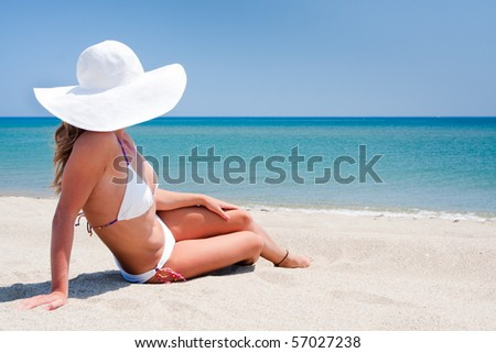Young woman enjoying the sun sitting on a beach close to the sea