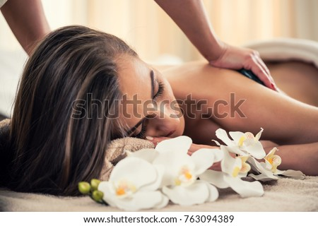 Young woman enjoying the therapeutic effects of a traditional hot stone massage at luxury spa and wellness center #763094389