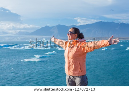 Young woman enjoying the view Jokulsarlon a lake in Iceland where icebergs collapsing from Vatnajokull glacier are floating around.