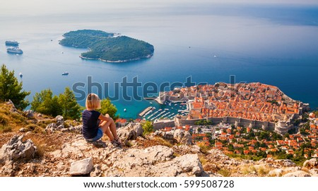 young woman enjoying the view of the Dubrovnik Old Town, sitting on the mountain above the city, Croatia #599508728
