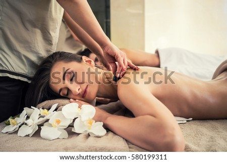 Young woman enjoying traditional hot stone massage next to her partner at luxury spa and wellness center