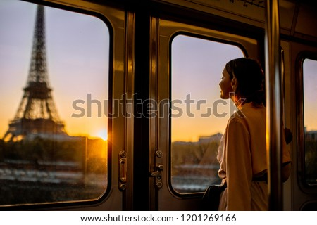 Young woman enjoying view on the Eiffel tower from the subway train during the sunrise in Paris Сток-фото ©