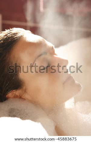 Young woman enjoys bath-foam in the bathtub.