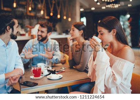 Young woman enjoys coffee with friends in a cafe #1211224654