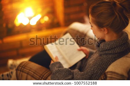 young woman enjoys reading a book by the fireplace on a winter evening #1007552188