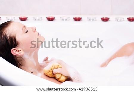 Young woman enjoys the bath-foam in the bathtub.