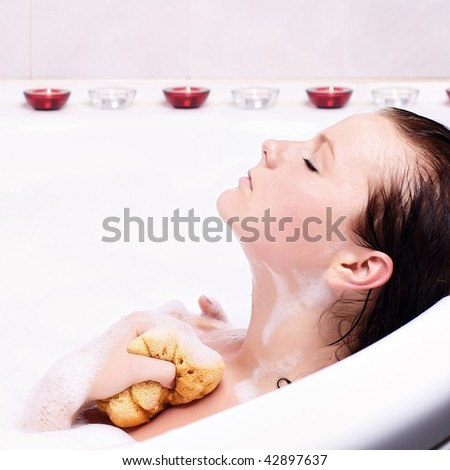 Young woman enjoys the bath-foam in the bathtub.