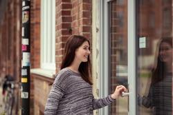 Young woman entering an urban building through a large glass door off an urban street