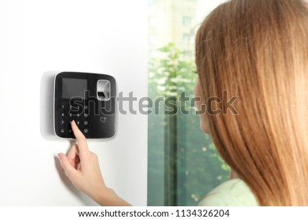 Young woman entering code on alarm system keypad indoors #1134326204