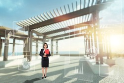 Young woman entrepreneur is standing indoors of a long bright futuristic passageway
