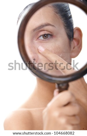 Young woman examining her skin by magnifying glass, looking for blackheads.