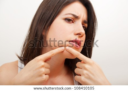 Young woman examining herpes in her face