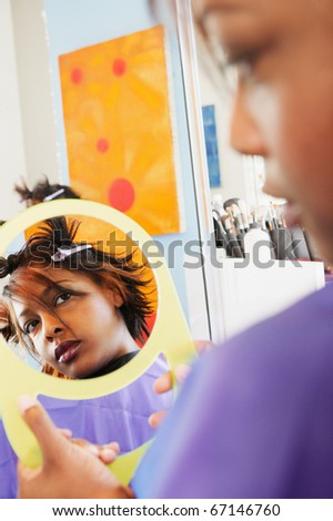 Young woman examining herself in the mirror