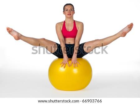 young woman exercise balance on pilates ball
