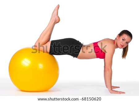 young woman exercise with yellow pilates ball