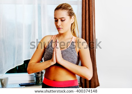 Young woman exercising and stretching her arms in living room #400374148