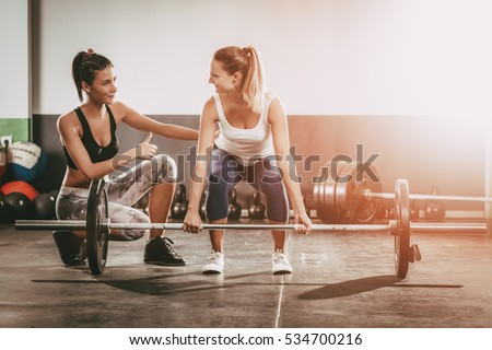 Young woman exercising at the gym with a female personal trainer.