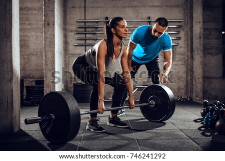 Young woman exercising at the gym with a personal trainer.