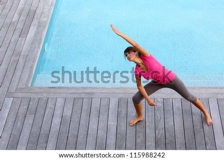 Young woman exercising by outdoor pool - stock photo