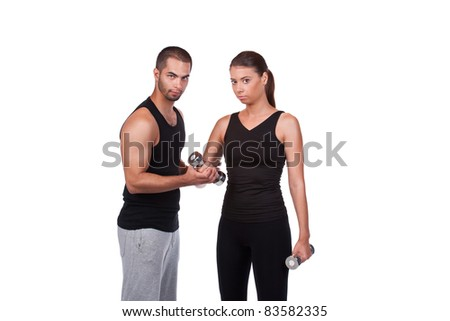 young woman exercising in gym with male instructor