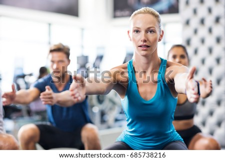 Young woman exercising in gym with people in background. Fit woman exercising with stretched hands and squats in modern gym. Fitness class exercising in gym.